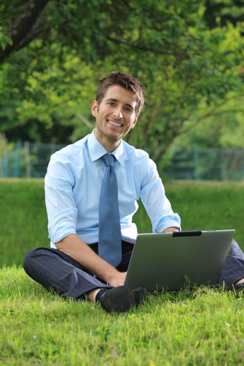 Smiling businessman working on laptop outdoors