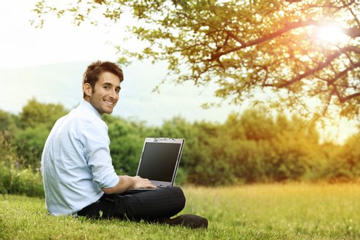 Businessman sitting on the grass is working on laptop
