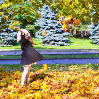 Little funny girl throws autumn leaves in the park on a sunny fall day