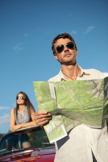 Handsome man holding a roadmap and looking away