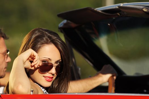 Portrait of a charming young woman in a convertible car