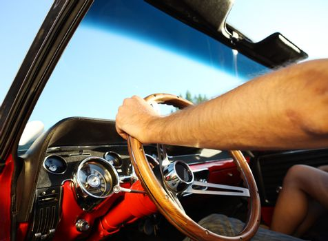 Driving a classic convertible car on a sunny day