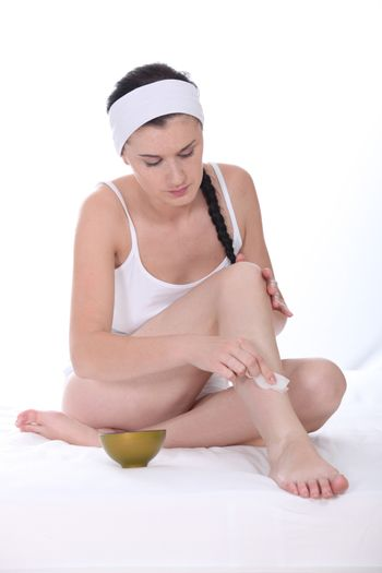 Woman applying beauty product to her legs