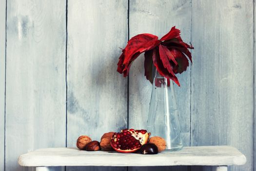 Photo of pomegranate, nuts and fall red leaves in vase