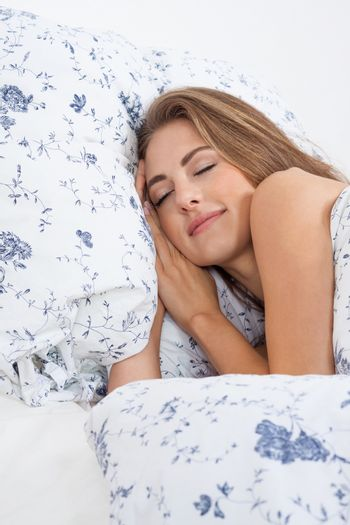 beautiful young woman sleeping in bed blue blanket