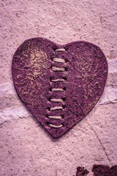 Romantic purple heart on a rough surface