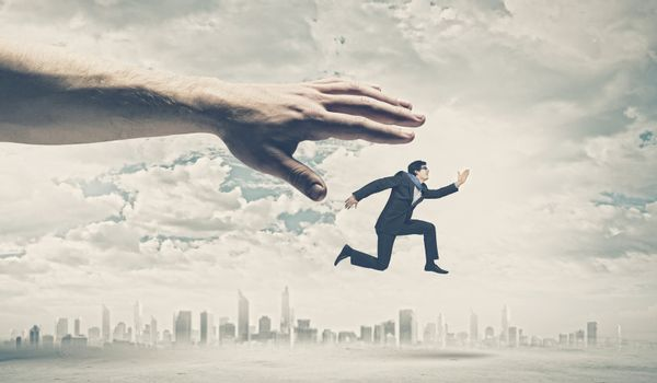 Big human hand catching businessman. Professional relations