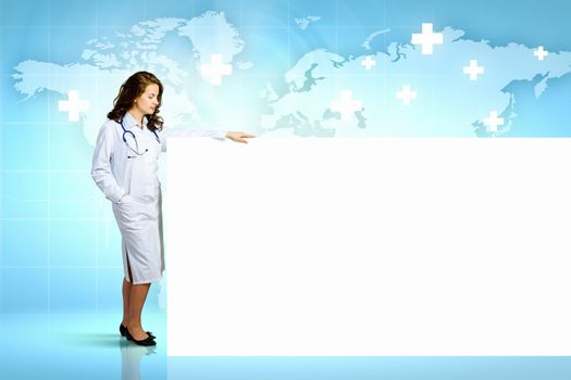 Image of young female doctor with blank banner. Place for text