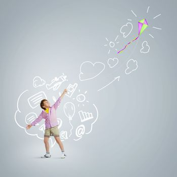 Little boy playing with kite against gray background. Childhood concept