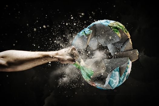 Close up image of human hand breaking earth planet