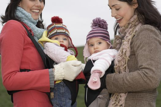 Two mothers in park with babies in slings standing face to face (mid section)