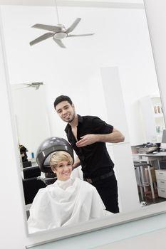 Woman under hair dryer at beauty salon