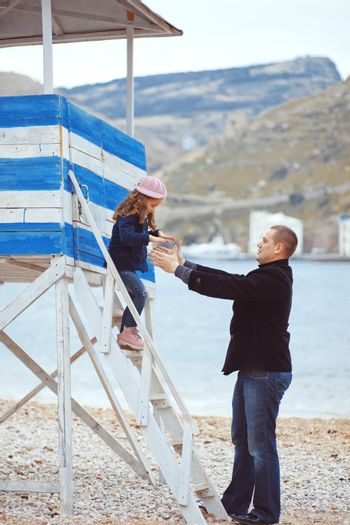Portrait of father with his daughter on berth near sea in the city, still life photo