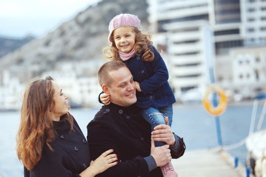 Portrait of happy young family walking with their child on berth near sea in the city, still life photo