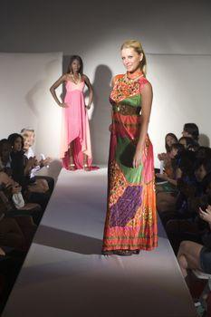 Woman in multicoloured dress on fashion catwalk