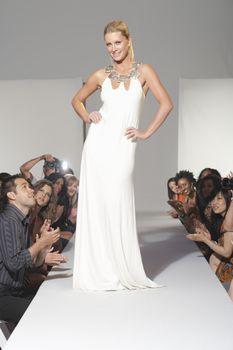 Woman stands in bridalwear on fashion catwalk