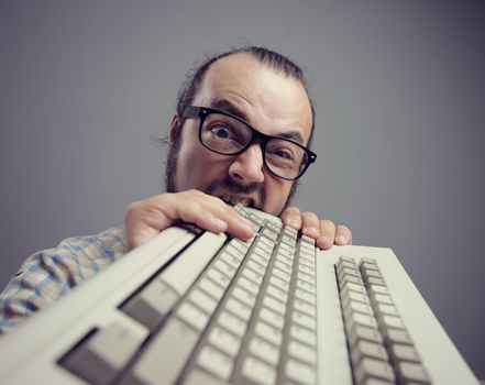 Eccentric angry man bites a keyboard