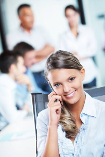 Portrait of a pretty young business woman at cell phone, meeting on background
