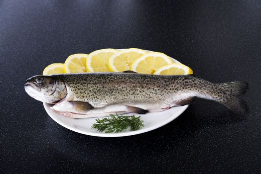 Fresh raw fish lying on a plate with lemon's slices.