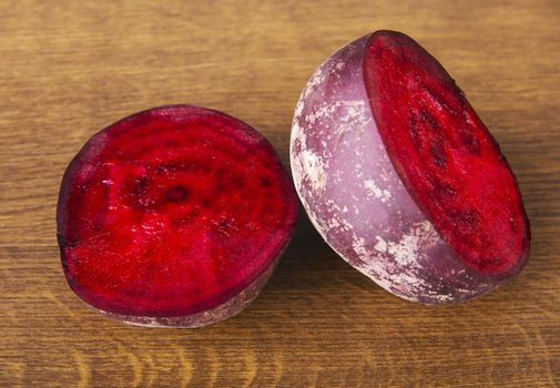 One beetroot divided into two. Over wooden background.