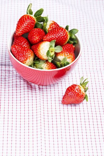 Fresh red strawberries in a bowl. Over kitches clothes background.