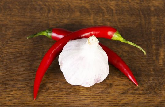 Two chili peppers lying with garlic over wooden background.