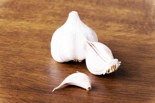 Fresh raw garlic lying on a wooden table.