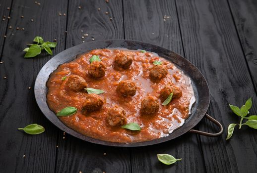 Italian cooking with beef meat balls in tomato sauce and basil