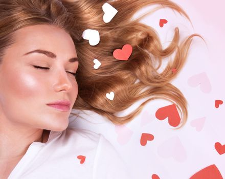 Closeup portrait of romantic fashion model lying down with closed eyes, beautiful long hair with red and white heart on it, Valentine day holiday