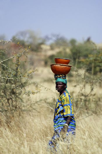the African women carrying heavy loads sometimes on their heads over long distances through the bush
