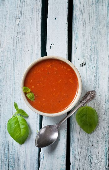 Tomato soup in rustic setting. Vegetable appetizer.