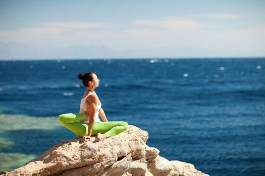 girl doing yoga on the beach