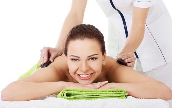 Beautiful woman lying on spa salon having stone massage. Spa concept.