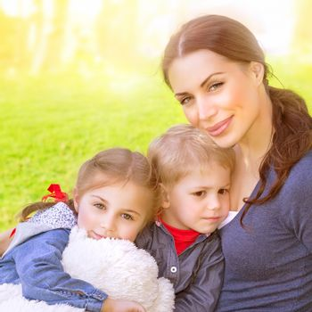 Closeup portrait of beautiful young mother with cute daughter and son sitting on the meadow, bright sun light, summer vacation, love and togetherness concept