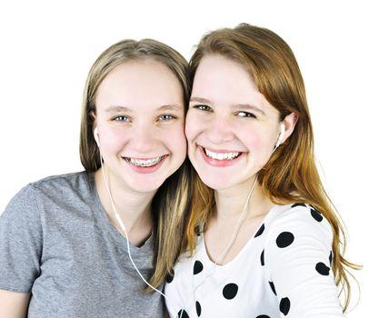 Portrait of two teenage girl friends listening to music sharing earphones