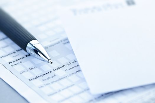 Blank credit application form with envelope and pen close up