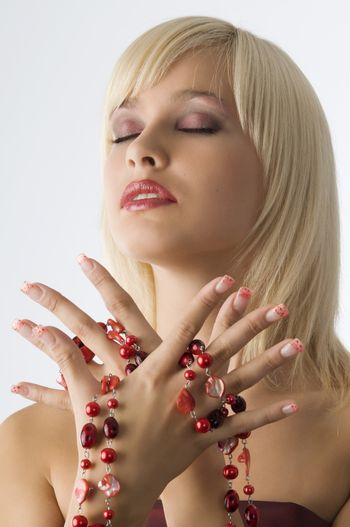 cute blond girl with glamor make up and red necklace around hands
