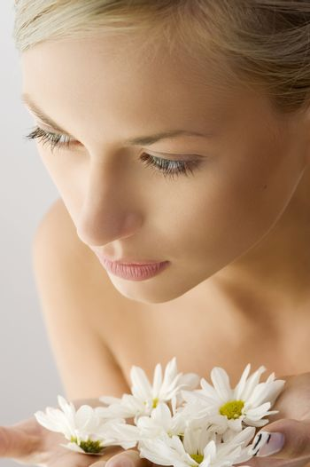 sweet beauty close up portrait of beautiful woman with some white daisy on hand