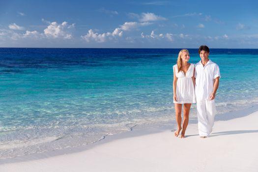 Happy couple walking along beautiful sandy beach, young family holding hands and enjoying honeymoon vacation on Maldives