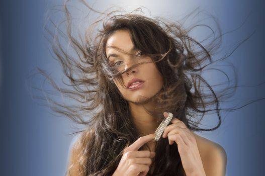 cute brunette playing with silver jewel and windly hair