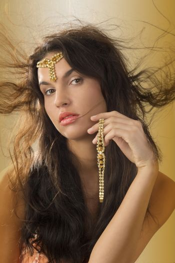 cute brunette with golden jewel and hair in wind
