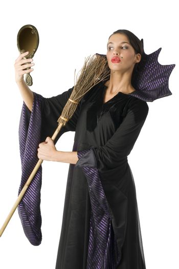 witch playing with a broom as a beauty brush