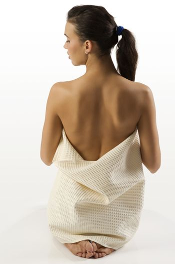 back side beauty portrait of a young cute brunette showing her nude shoulder