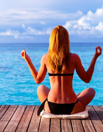 Back side of attractive girl doing yoga exercise on seashore, sitting in lotus position and enjoying peaceful view, summer vacation, zen balance concept
