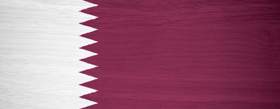 Qatar flag on wood texture