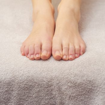 Beautiful female feet on a towel after pedicure treatment at spa.