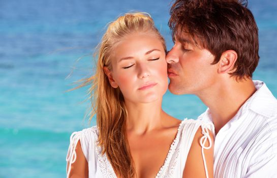Romantic couple kissing on the beach, close-up faces portrait of two in love, young people relaxing outdoor on summer holidays on Maldives islands, family on honeymoon vacation