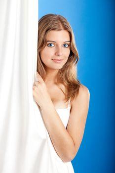 Beautiful young woman peeking behind a white sheet