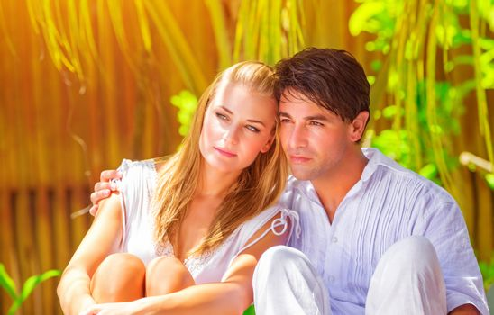 Portrait of young family spending honeymoon on tropical resort, sitting in palm trees park, romantic summer vacation, love and tenderness concept