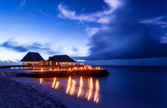 Romantic restaurant on the beach, beautiful night seascape, luxury resort on Maldives, dark blue sky, summer vacation concept